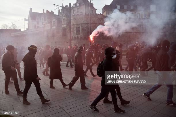 TOPSHOT Protesters wear masks during clashes with French police on the edge of a demonstration against the visit of French presidential election...