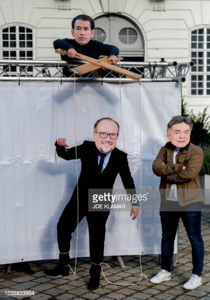 Protesters wear masks of Austria's former Chancellor Sebastian Kurz as a puppeteer, operating a marionette featuring Austria's new Chancellor...