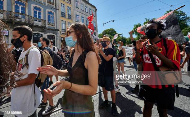 Protesters wear protective masks and hold sings and banners during a rally to demonstrate against Fascism, Nazism and racism on July 25, 2020 in...