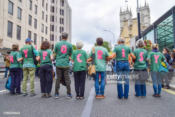 Protesters wear shirts with letters spelling out 'Hypocrisy' during the demonstration outside the Department for Business, Energy and Industrial...