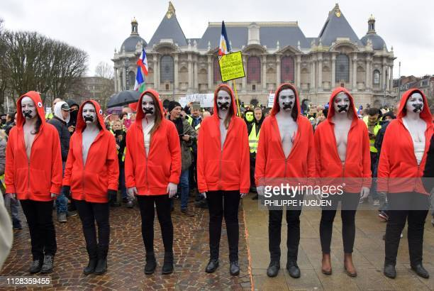 TOPSHOT Protesters wearing a tricolor cockade on their hood an emblem referring to the French Revolution stand with their mouth taped during an...