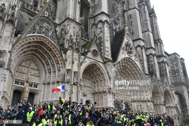 Protesters wearing a yellow vest gather outside the Bourges Cathedral during an antigovernment demonstration called by the Yellow Vest movement in...