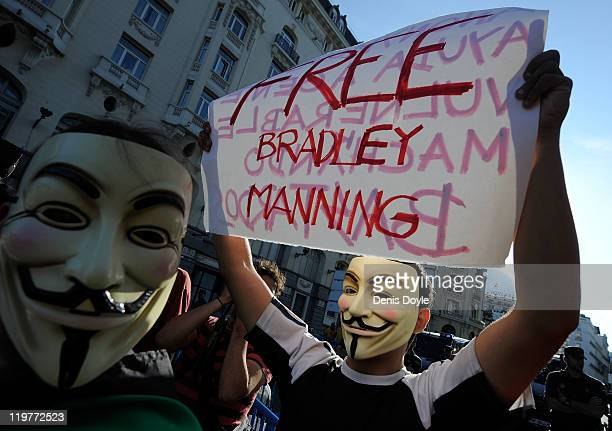 Protesters, wearing anonymous masks, hold up a sign demanding the release of Bradley Manning, the U.S. Soldier accused of passing restricted material...