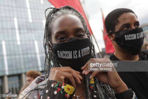 Protesters wearing face coverings with racism is a virus written as a message on the fabric attend a demonstration outside the US Embassy in London...