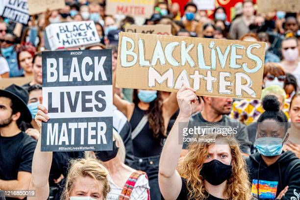Protesters wearing face masks are seen holding protest placards with antiracist messages during the Black Lives Matter protest in Amsterdam Thousands...