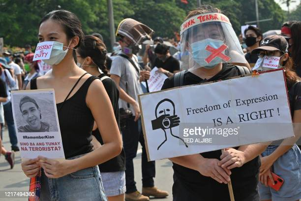 Protesters wearing face masks carry placards as they join a protest march at a university campus in Manila on June 4 a day after congress passed an...