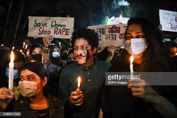 Protesters wearing face masks hold lit candles during the demonstration. Female activists and classmates take part in a candlelight protest demanding...