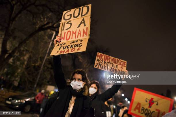 Protesters wearing face masks hold placards during the protest. Tens of thousands of people took to the streets of Poland for a ninth straight day of...
