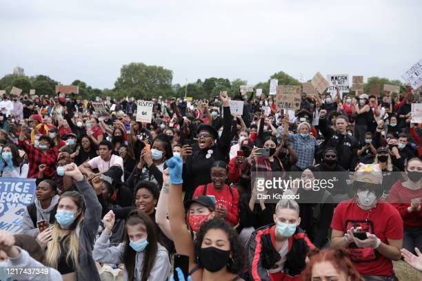 Protesters wearing face masks hold up placards and raise clenched fists during a Black Lives Matter protest in Hyde Park on June 3 2020 in London...