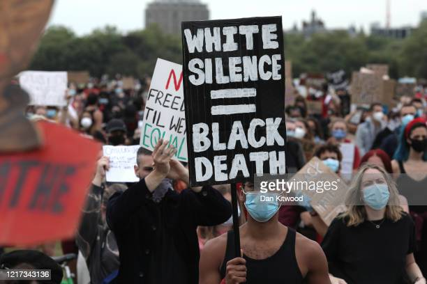Protesters wearing face masks hold up signs during a Black Lives Matter protest in Hyde Park on June 3 2020 in London United Kingdom The death of an...