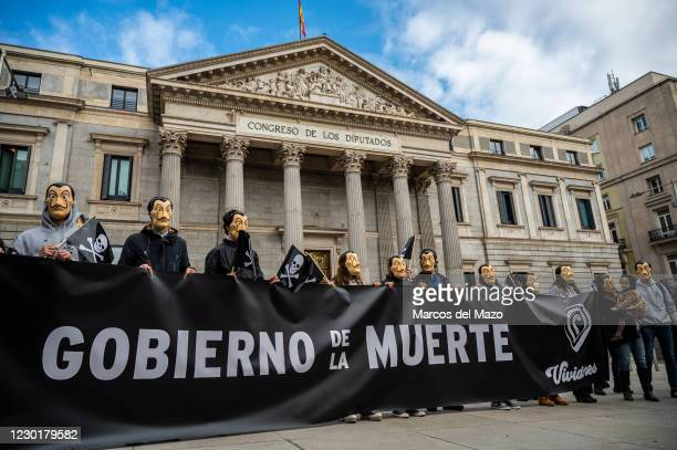 Protesters wearing face masks of Dali and carrying a banner reading 'Government of the death' during a demonstration against euthanasia in front of...
