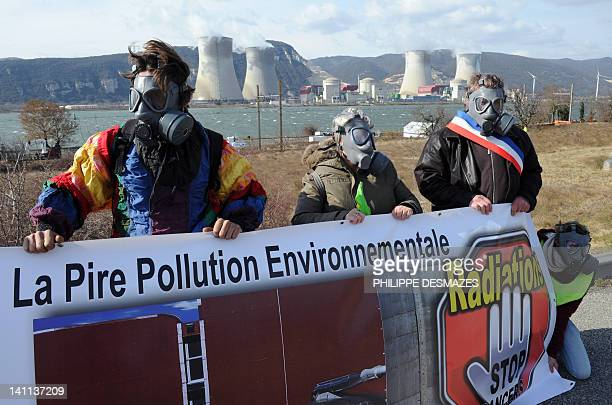 Protesters wearing gas masks gather and create a human chain in front of the CruasMeysse nuclear plant along the N7 national road to call for the...