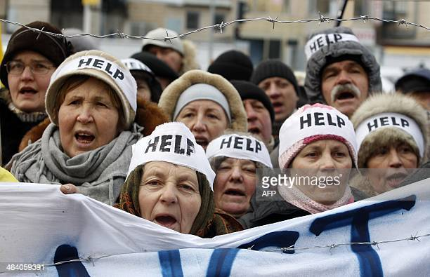 Protesters wearing headbands reading Help shout slogans during an action entitled Impose sanctions stop the violence in front of the European Union...