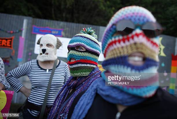 Protesters wearing knitted balaclavas protest at the fence near the G8 Summit at Lough Erne Resort in Enniskillenin Northern Ireland on June 17 2013...