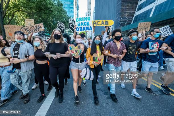 Protesters wearing masks and holding signs and pictures of George Floyd march arm in arm in a single line as they pass Bryant Park, This was part of...