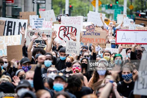 Protesters wearing masks and holding up signs of support and their hands in Foley Square Protesters sat on the ground at Foley Square in a show of...