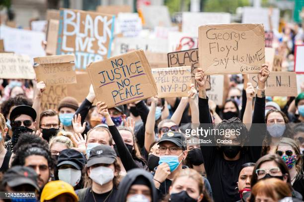 Protesters wearing masks and holding up signs that say No Justice No Peace George Floyd Say His Name White Silence = Violence as they sit on the...