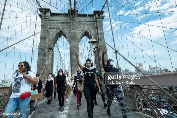 Protesters wearing masks and holding up their fists with one wearing a shirt that says Muhammad Ali with the Arches of the Brooklyn Bridge behind...