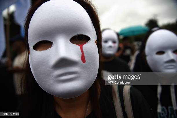 Protesters wearing masks depicting victims of extra judicial killings take part in a demonstration against the killings of suspected drug users...