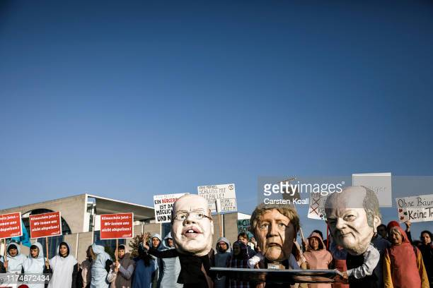 Protesters wearing masks featuring, German Economy Minister Peter Altmaier, , German Chancellor Angela Merkel and German Finance Minister and...