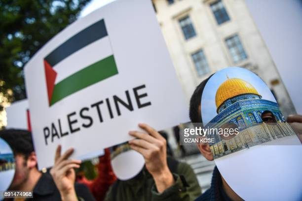 Protesters wearing masks featuring Jerusalem's Dome of the Rock Mosque take part in a protest against the US recognition of Jerusalem as Israel's...