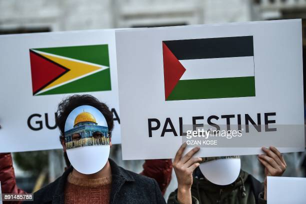 Protesters wearing masks featuring Jerusalem's Dome of the Rock Mosque and holding a placard depicting the Palestinian flag, take part in a protest...