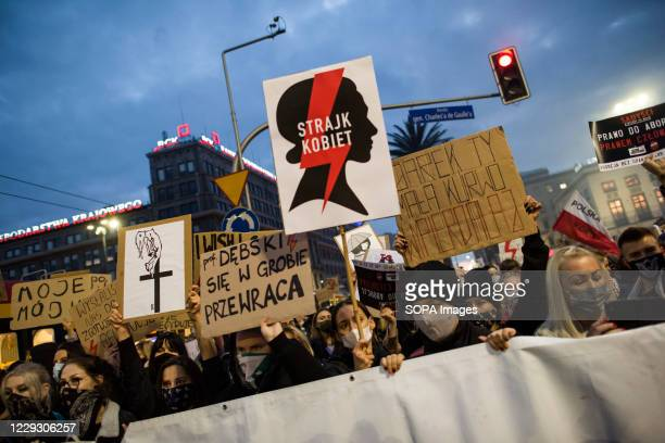 Protesters wearing masks hold placards and chants anti government slogans during the protest. Thousands of people took to the streets of Poland for a...