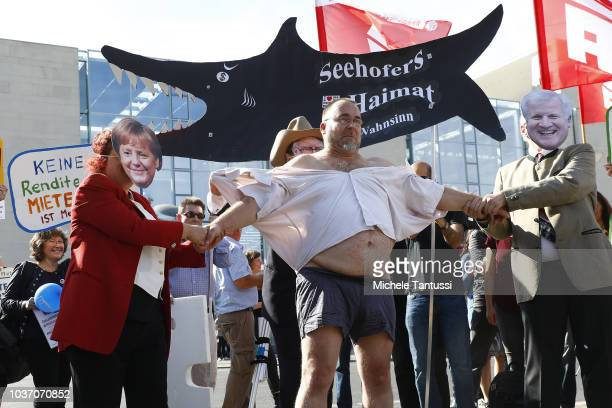 Protesters wearing masks of chancellor Merkel Minister Seehofer and investor Warren Buffet demonstrating for affordable housing gather outside...