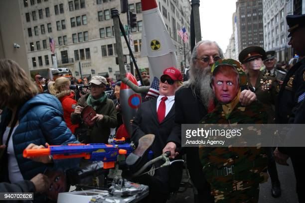 Protesters wearing masks of Donald Trump and Vladimir Putin attend the April Fools Day Parade by Trump Tower on the Fifth Avenue in New York City...