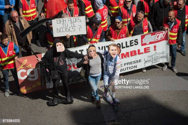 Protesters wearing masks of French presidential candidate Emmanuel Macron and his wife Brigitte Trogneux and a demonstrator dressed as the Grim...