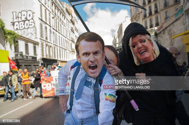 Protesters wearing masks of French presidential candidates Emmanuel Macron and Marine Le Pen depicted as the Grim Reaper lead a march marking the...