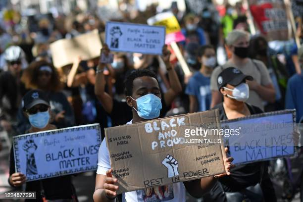 Protesters wearing protective face coverings hold placards as they march down Park Lane in support of the Black Lives Matter movement in London on...