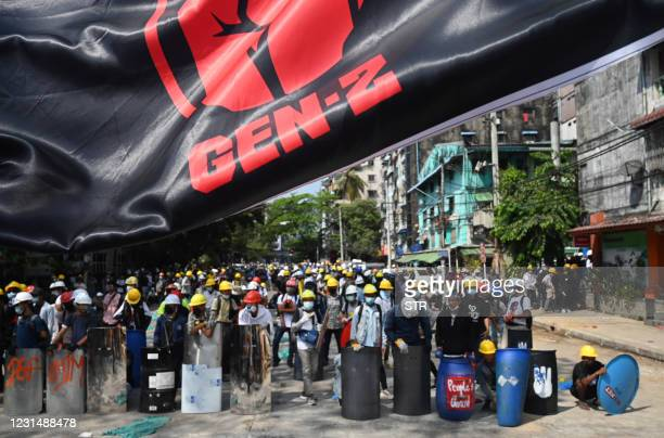 """Protesters wearing protective gear gather on a road, next to a banner that reads """"Gen-Z"""", during a demonstration against the military coup in Yangon..."""