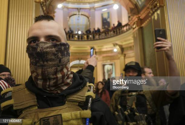 Protesters wearing protective masks gather outside the doors of the chamber room at the Michigan Capitol Building in Lansing, Michigan, U.S., on...