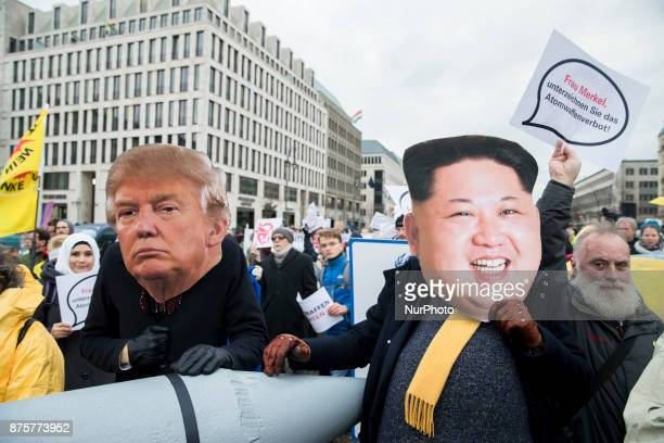 Protesters wearing the masks of US President Donald Trump and North Korean dictator Kim Jongun attend a demonstration organized from awarded Nobel...