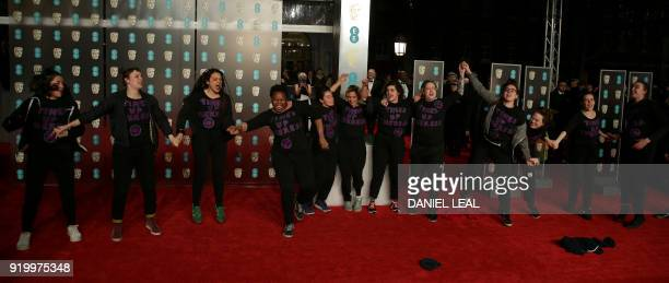 Protesters wearing TShirts that read 'Times Up Theresa' get onto the red carpet at the BAFTA British Academy Film Awards at the Royal Albert Hall in...