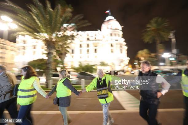 Protesters wearing yellow jackets form a human chain in protest against the rising of the fuel and oil prices in front of the Negresco hotel on the...