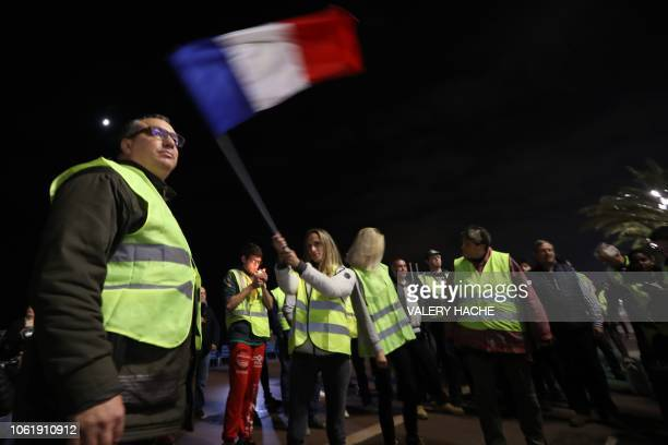 A protesters wearing yellow jackets waves a French flag during a protest in front of Negresco hotel on the 'Promenade des anglais' water front in...