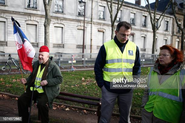 Protesters wearing 'Yellow Vest' and holding a French flag gather in a street in Versailles outside Paris on December 22 2018 The 'Yellow Vests'...