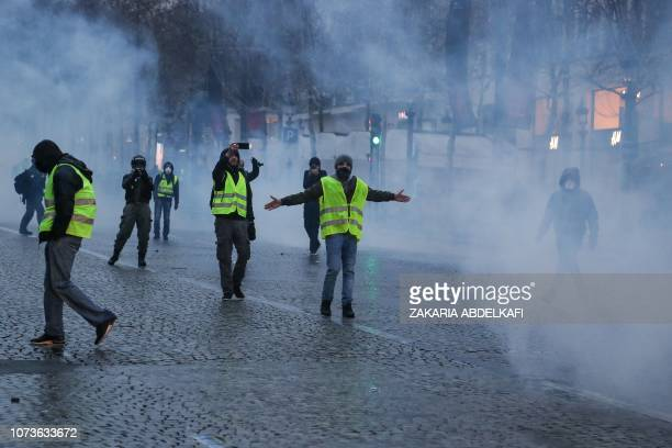 Protesters wearing yellow vest gesture amid smoke in front of police forces during a demonstration against rising costs of living blamed on high...