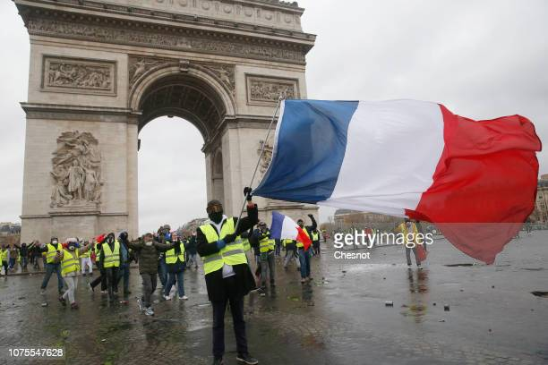 Protesters wearing Yellow Vests and holding a French flag near l'Arc de Triomphe on December 01, 2018 in Paris, France. The 'Yellow Vest' is a...