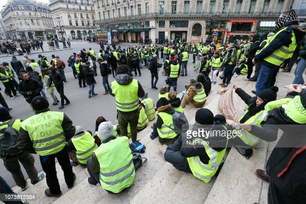 Protesters wearing yellow vests demonstrate in front of the Opera Garnier in Paris against rising costs of living blamed on high taxes on December 15...