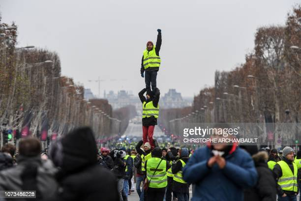 Protesters wearing yellow vests do a human pyramide as they demonstrate against rising costs of living they blame on high taxes in Paris, on December...