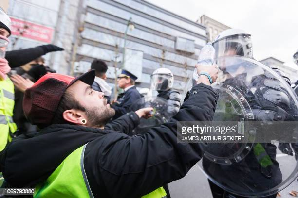Protesters wearing yellow vests face riot police as they take part in a protest in Brussels on December 8 2018 The socalled gilets jaunes protest...