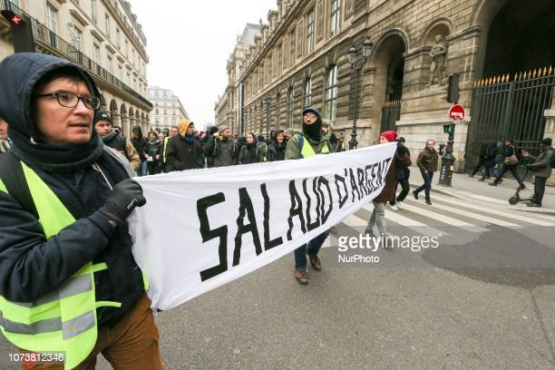Protesters wearing yellow vests hold a banner reading « Bastard of money » in front of the Louvre Museum during a demonstration in Paris on December...