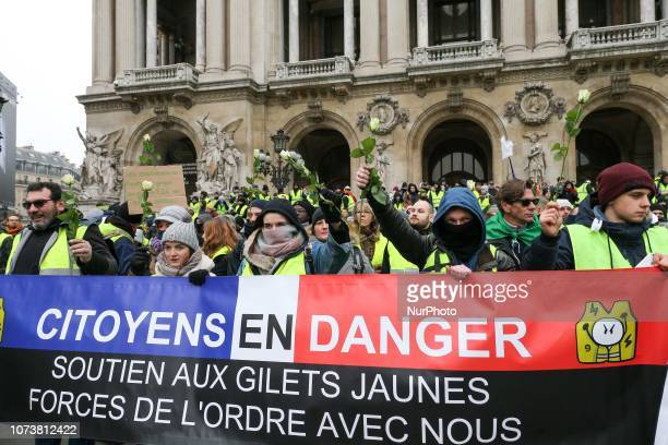 Protesters wearing yellow vests hold a banner reading « People in danger Support for yellow vests Police with us » during a demonstration in front of...