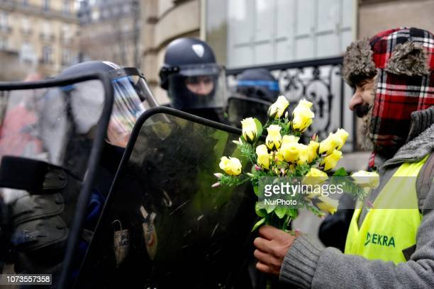 A protesters wearing yellow vests holds flowers as she arrives to demonstrate in the center of Paris on December 15 2018 to protest against rising...