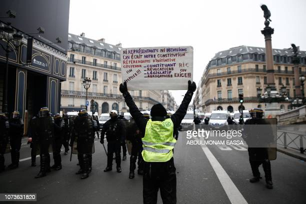 Protesters wearing yellow vests holds up a cardboard reading 'Neither represented nor invited to talks we are writing to change our Constitution...