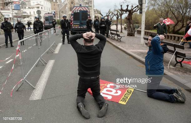 Protesters wearing yellow vests reenact the arrest of dozens of highschool pupils kneeling with their hands behind their heads during a mass roundups...