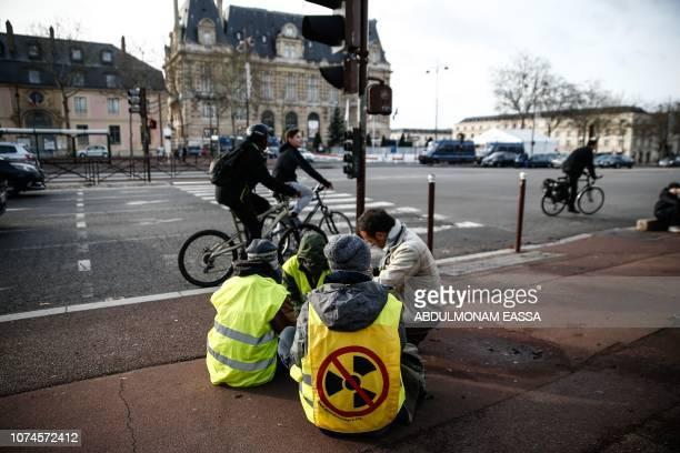 Protesters wearing 'Yellow Vests' sit in a street near the Chateau de Versailles in Versailles outside Paris on December 22 2018 The 'Yellow Vests'...